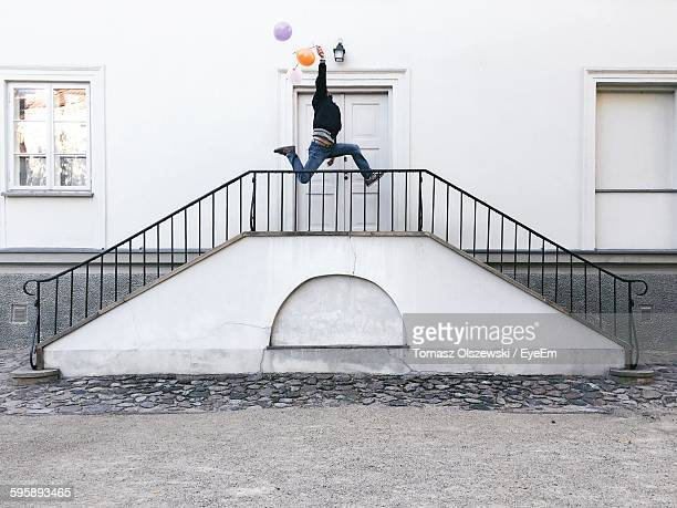 Man With Balloon Jumping Over Steps By Door Of Building