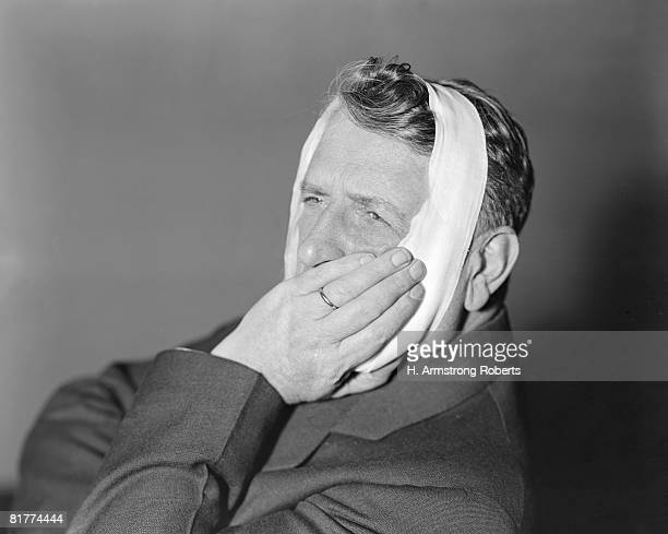 man with bandage around head, holding jaw. - mumps stock pictures, royalty-free photos & images