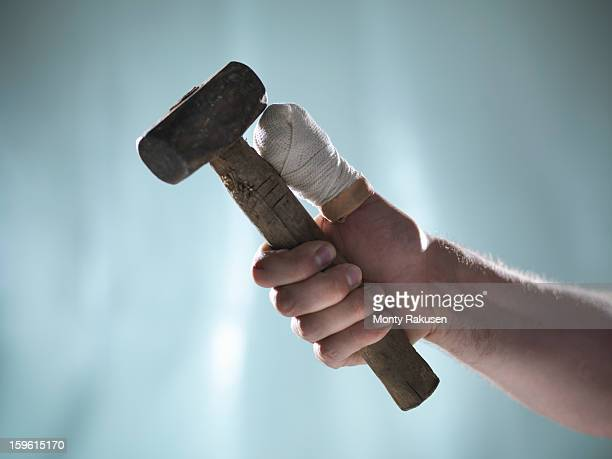 Man with bandaged thumb holding hammer