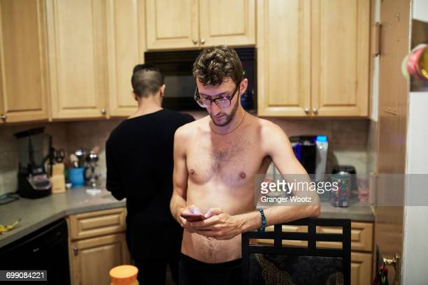 Man with bare chest texting on cell phone in kitchen