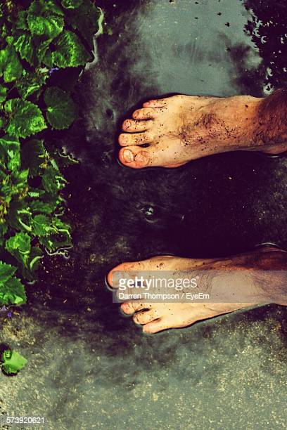 Man With Barefoot Standing On Puddle