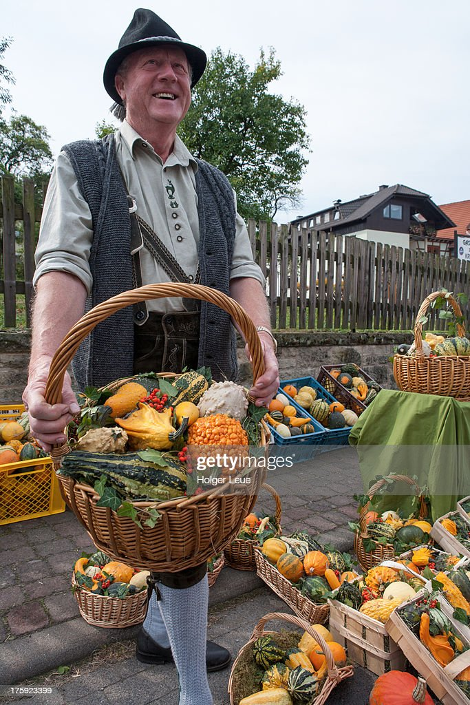 Man with basket of pumpkins at harvest festival : Stock Photo