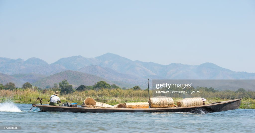 Man With Basket Sitting In Boat On Lake Against Sky : Photo