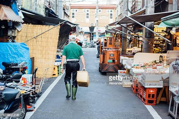 Man with basket walking among stalls at Tsukiji fish market, Tokyo, Japan