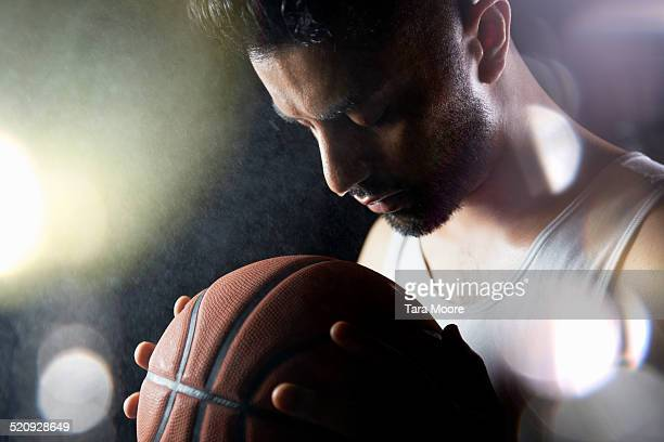 man with basketball in rain