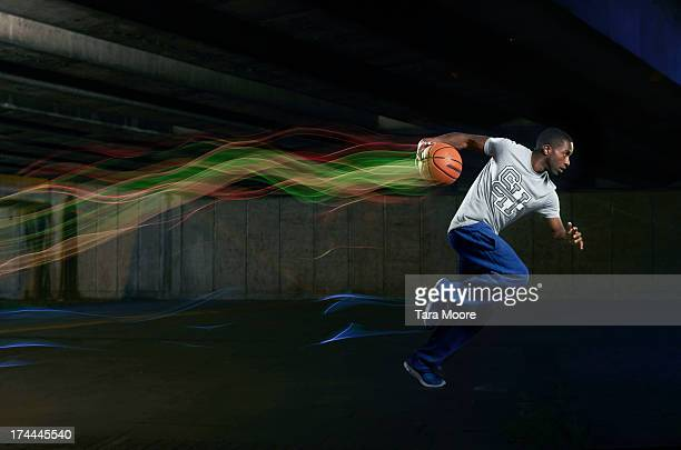 man with basketball running with light trails