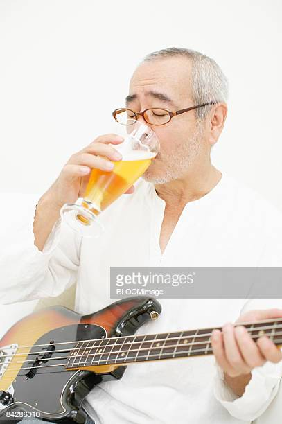 Man with bass guitar having beer