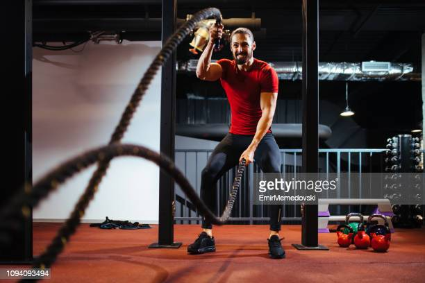 homem com cordas de batalha exercitando na academia - dureza - fotografias e filmes do acervo