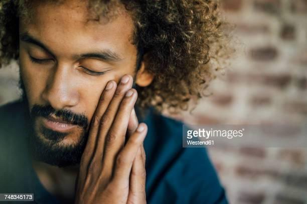 man with beard and curly hair closing his eyes - augen geschlossen stock-fotos und bilder