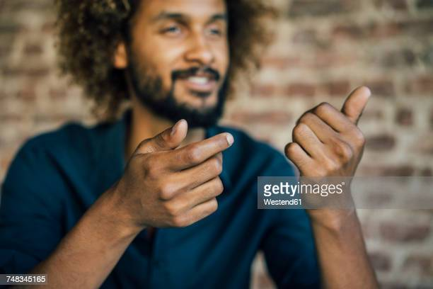 man with beard and curly hair gesticulating - onscherpe achtergrond stockfoto's en -beelden