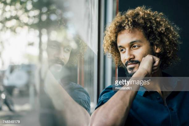 Man with beard and curly hair looking out of window