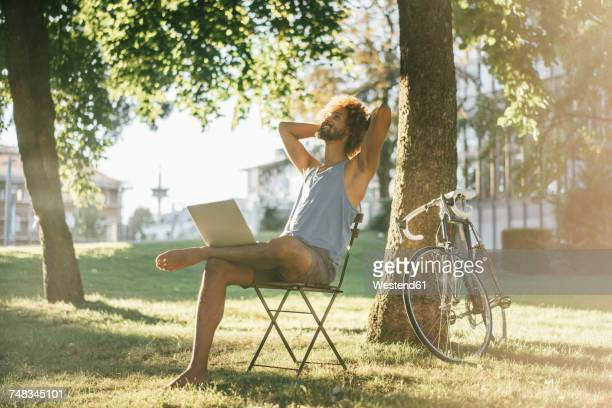 Man with beard and curly hair using laptop in park