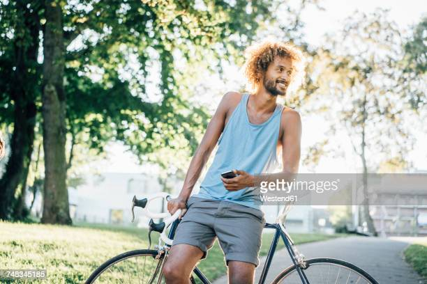 man with beard and curly hair with bicycle in park - three quarter front view stock pictures, royalty-free photos & images