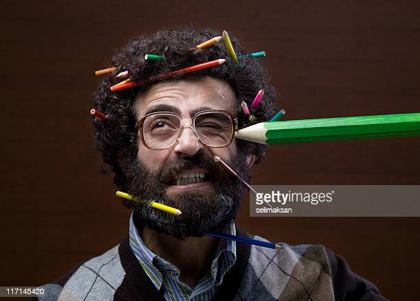 Man with beard, curly hair has many crayons in head