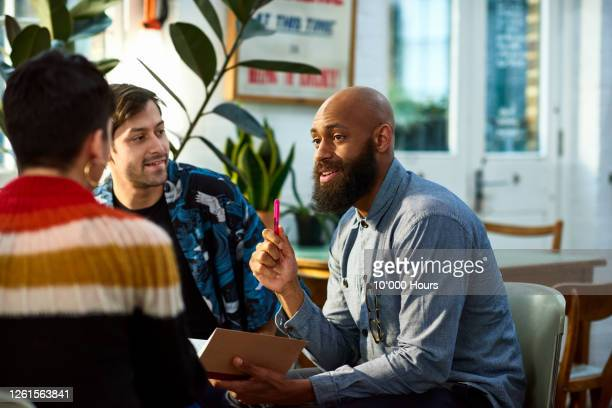 man with beard discussing with team - office stock pictures, royalty-free photos & images