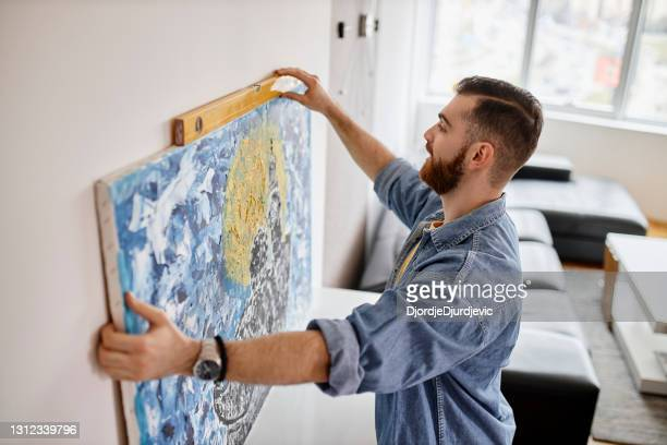 man with beard hanging a painting on the wall at his living room - hanging stock pictures, royalty-free photos & images