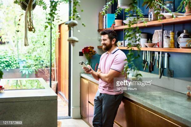 man with beard holding phone in stylish kitchen - domestic life stock pictures, royalty-free photos & images
