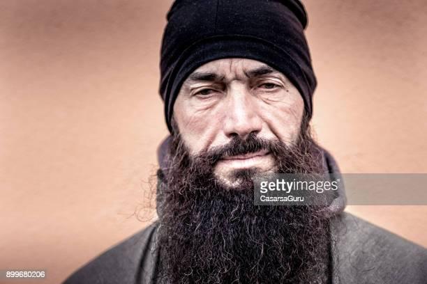 Man met baard In de opwarming van de aarde kleren op oranje achtergrond