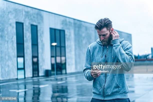 Man with beard listens to music on smart phone outside