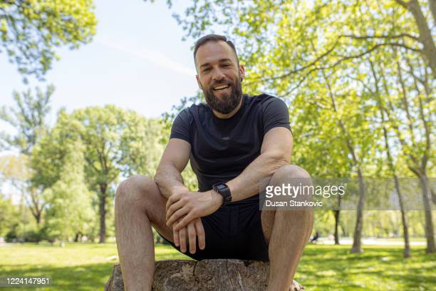 man with beard relaxing in the park after workout - dusan stankovic stock pictures, royalty-free photos & images