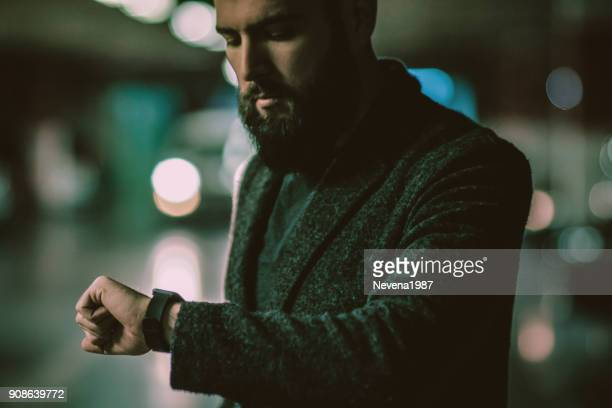 man with beard waiting and looking at watch - one man only stock pictures, royalty-free photos & images