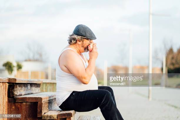 man with beer belly sitting on steps and eating a sandwich - snag tree stock pictures, royalty-free photos & images