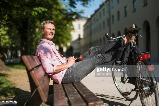 Man with bicycle and old-fashioned camera relaxing on a park bench