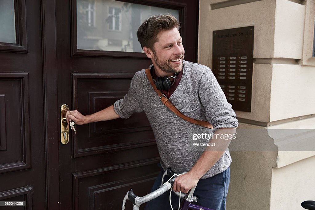 Man with bicycle at front door : Stock Photo