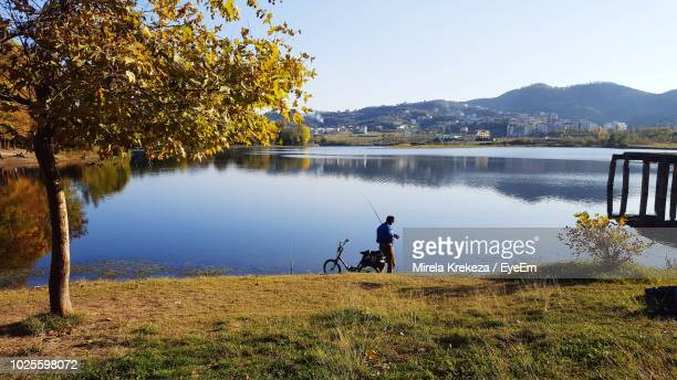 man with bicycle by lake against sky - tirana stock pictures, royalty-free photos & images