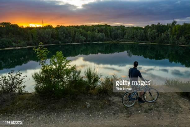 man with bicycle in beautiful sunset - colónia renânia imagens e fotografias de stock