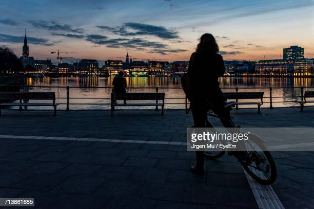 man with bicycle on river in city at sunset - hamburg germany stock pictures, royalty-free photos & images