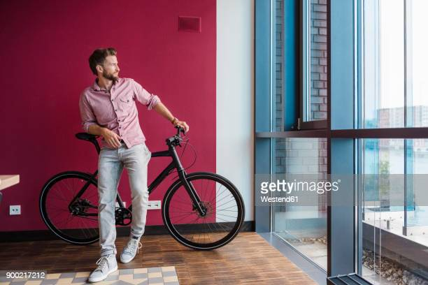 man with bicycle standing in modern office looking out of window - lehnend stock-fotos und bilder