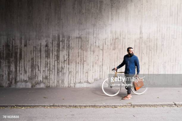 Man with bicycle standing in tunnel