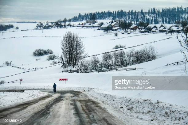 Man With Bicycle Standing On Road Amidst Snow Covered Mountain Against Sky