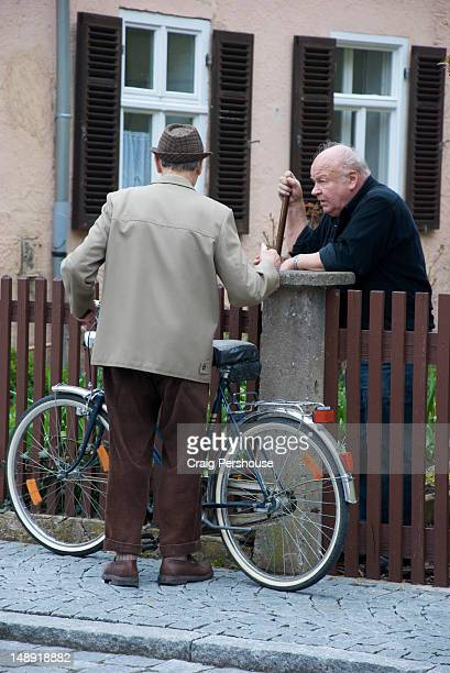 Man with bicycle talking with neighbour.