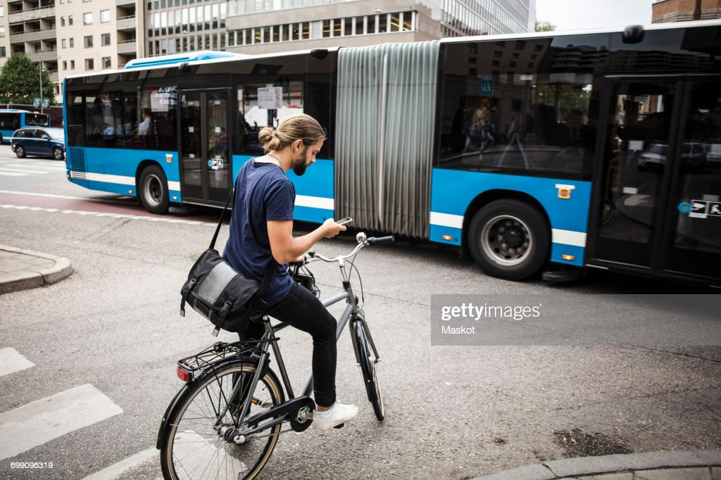 Man with bicycle using mobile phone while standing on city street against articulated bus : Stock Photo