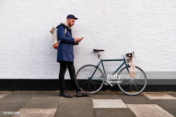 man with bicycle using smart phone while leaning on wall - side view stock pictures, royalty-free photos & images