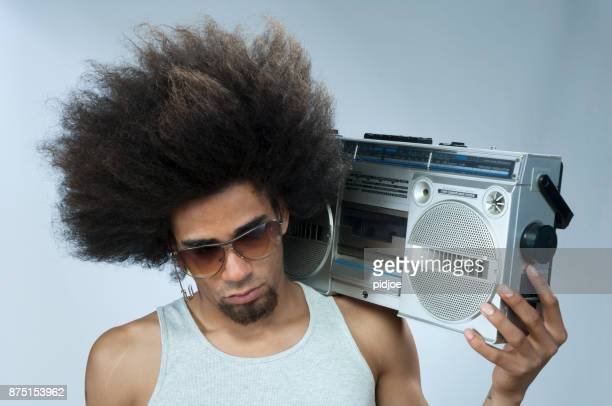 Man with big afro hair  listening to funky music on ghetto blaster