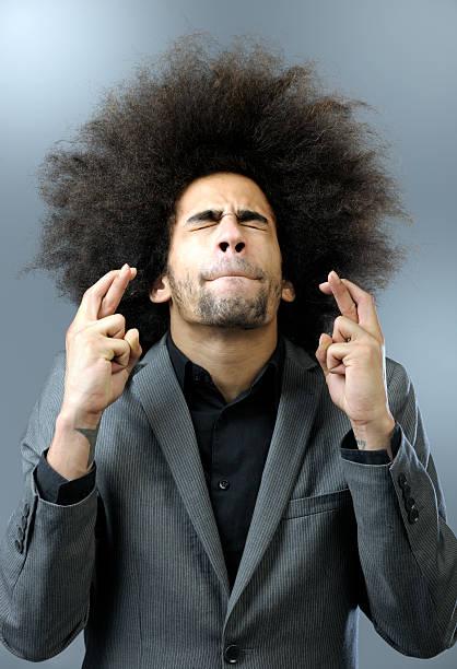 homme avec cheveux volumineux en gardant les doigts croisés - croiser les doigts photos et images de collection