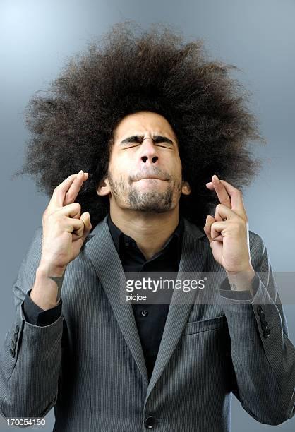 Mann mit großen Haar hält Finger kreuzen