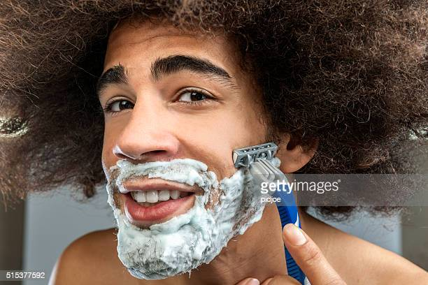 man with big hair shaving beard
