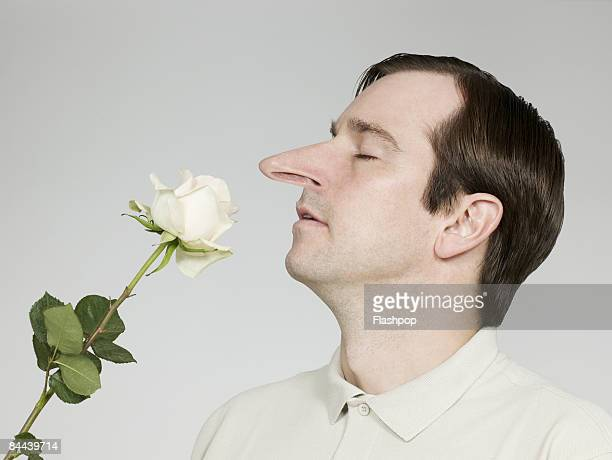 Man with big nose smelling rose