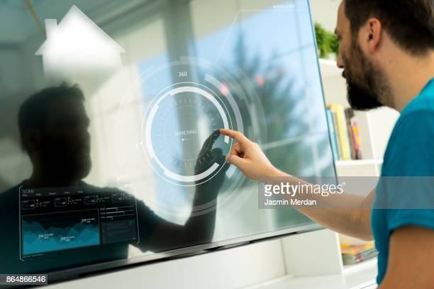 man with big touch screen for smart home functions - house icon stock pictures, royalty-free photos & images