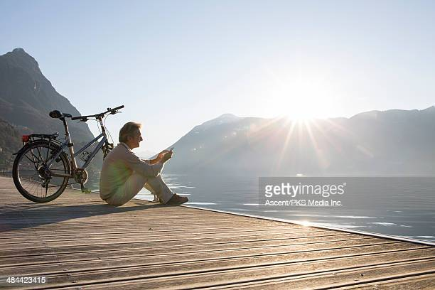 Man with bike rests on wooden wharf, sends text