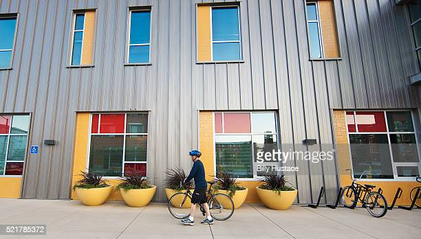 Man with bike walking in front of a colorful building, in a Zero Net Energy community