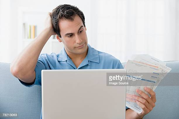 Man with bills and a laptop computer