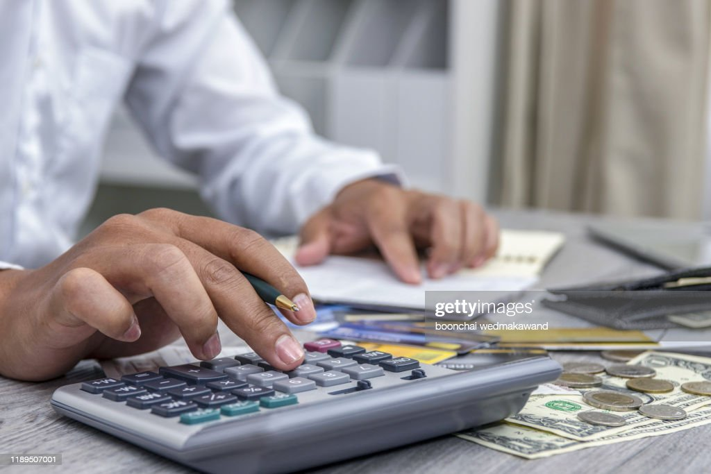 Man with bills and calculator. man using calculator to calculate bills at the table in office. Calculation of cost : Foto de stock