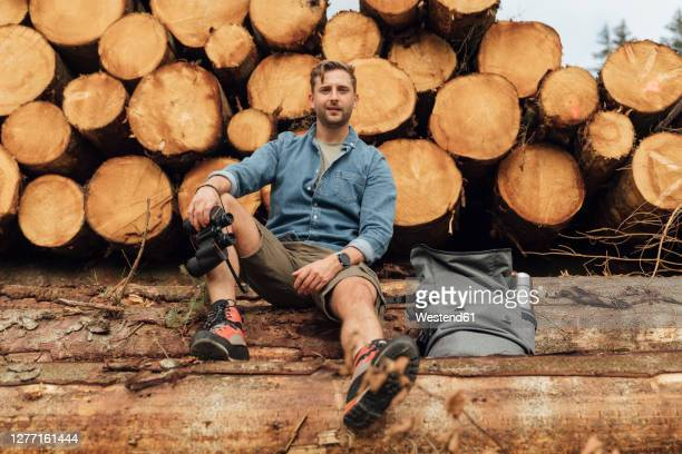 man with binoculars and backpack sitting on log against woodpile in forest - binoculars stock pictures, royalty-free photos & images