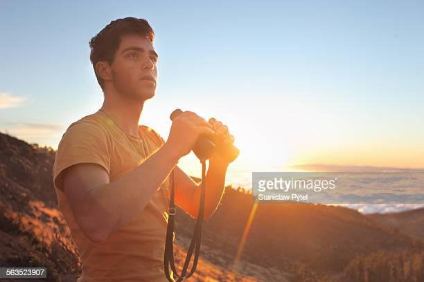 Man with binoculars at sunset in mountains