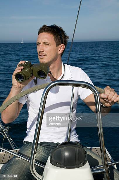 A man with binoculars at the helm of a yacht